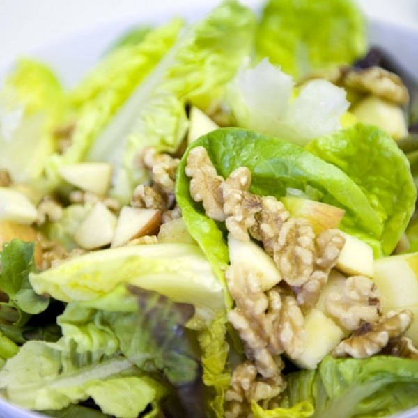 A tasty looking bowl of salad leaves, walnuts and apples