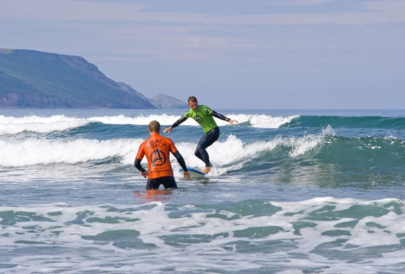 Adult beginner surfer on stag weekend riding wave towards instructor