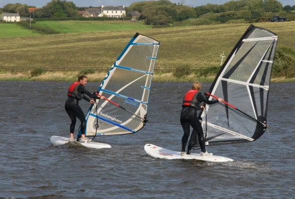 Families windsurfing behind each other on lake nr Bude
