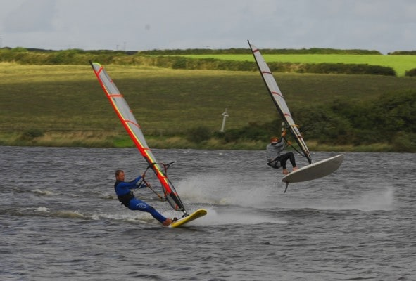 Windsurfer jumping on activities lake