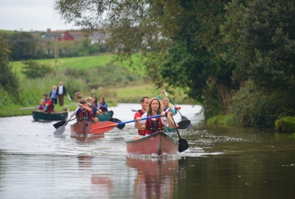 5 canoes meandering down the canal on family activity day