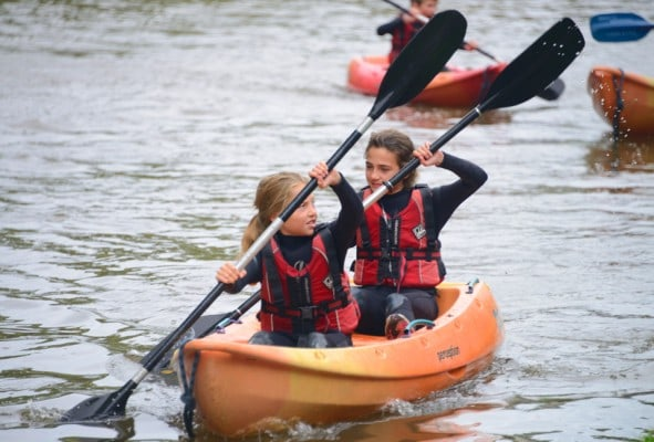Adventurous children forward paddling their kayak