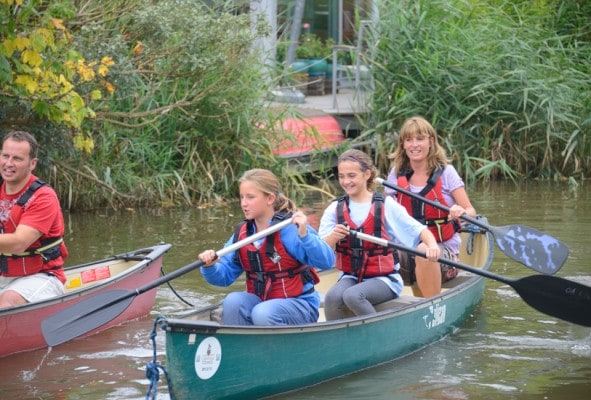 Mum and daughters paddling a canoe in unison
