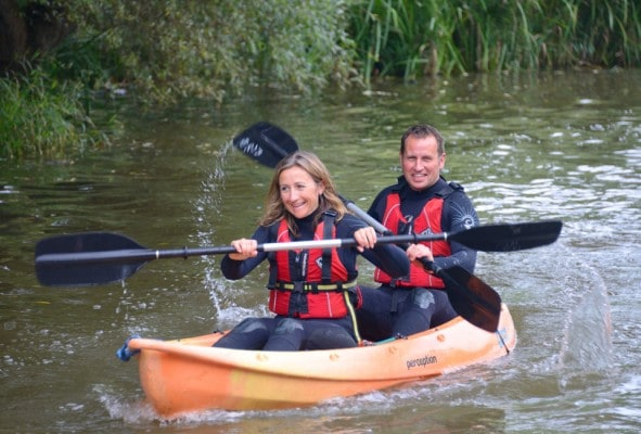 Parents journeying on kayaks down Bude