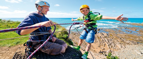 Yr6 boy on activity trip leaning backwards off sea cliff abseil with arms held out to the side