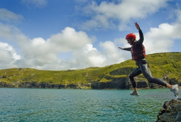 Coasteering man leaping off cliff ledge into the Atlantic Ocean