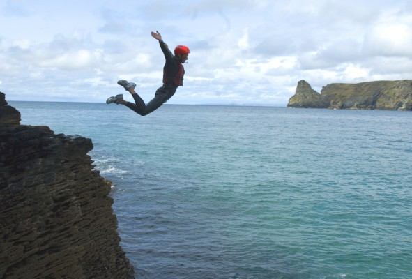Huge Coasteering leap from headland into blue crystal clear ocean