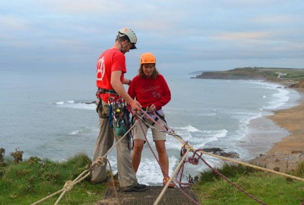 Outdoor Adventure abseil instructor guiding hen lady backwards off the top of the sea cliff