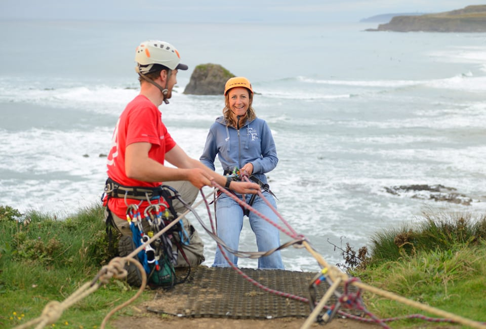Woman trying abseiling on her family activity holiday in Widemouth Bay, England