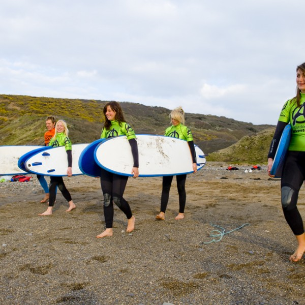 Hen group surf lesson carrying surf boards on Widemouth Beach