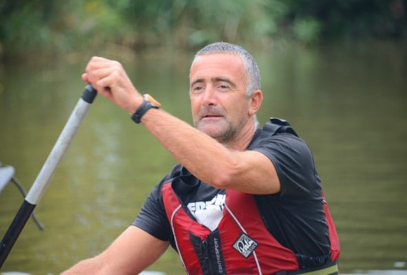 Close up of man paddling a canoe on adventure weekend