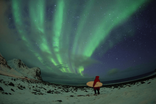 Northern lights on surfer's head in the Arctics, Lofoten Islands, air temperature 1C, water temperature 5C