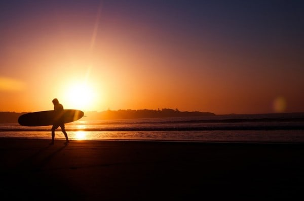 A surfer walking on the beach with a longboard in the sunset