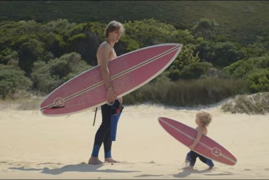 Surfing man and baby on adventure holiday in latest Evian advert