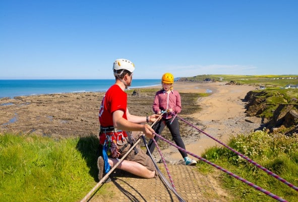 A visitor to Outdoor Adventure abseiling with one of our trained instructors