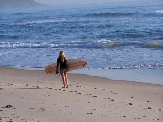 A female surfer holding a surfboard on the beach near Outdoor Adventure