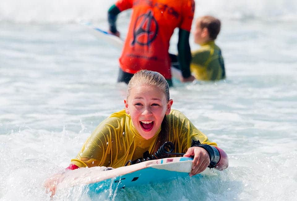 Girl bodyboarding on her family activity holiday in Bude Cornwall