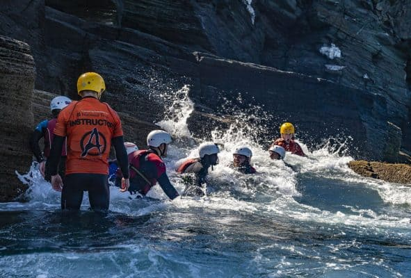 A group coasteering enjoying being washed around by the waves
