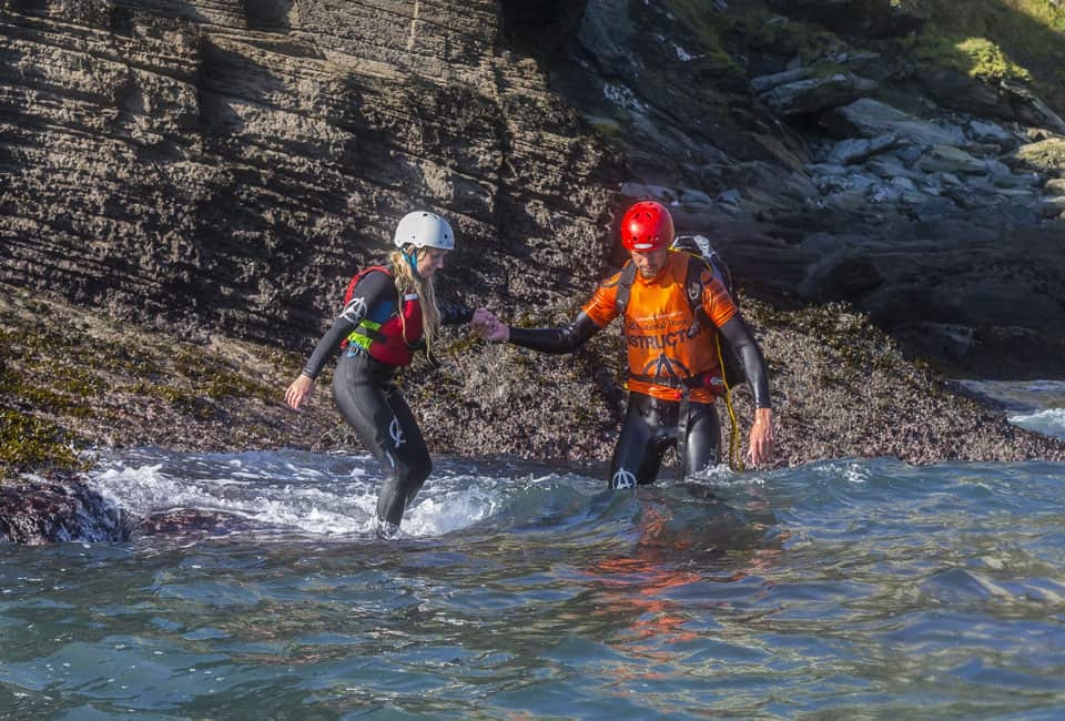 Coasteering instructor helping young lady around a rock ledge