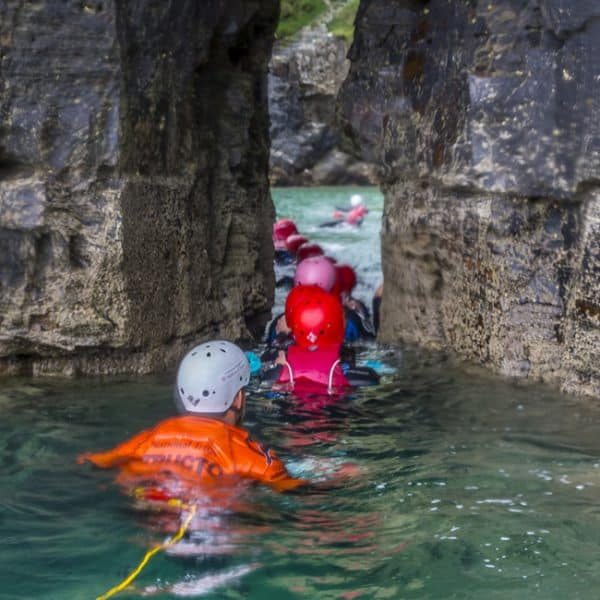 Coasteering instructor follows his group through a natural arch