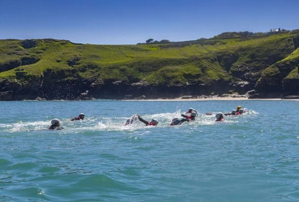 Swimming back to the start of a coasteering session near Tintagel in Cornwall