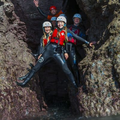 Group coasteering exploring a cave near Bude