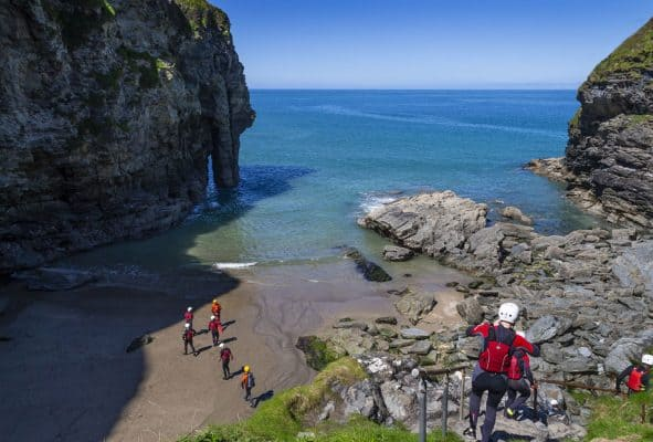 A group of people descending into Bossiney Cove at the start of their coasteering session