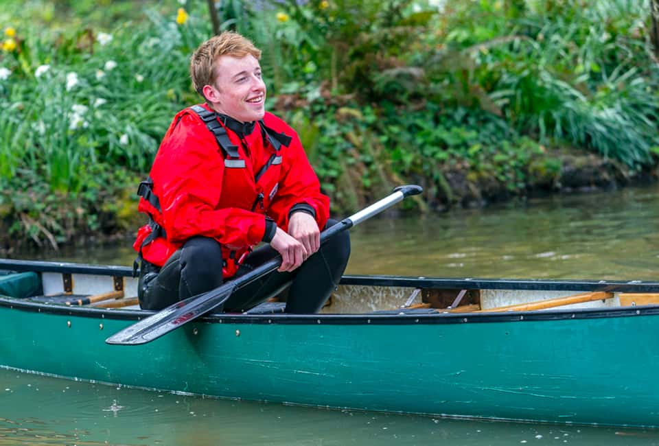 outdoor instructor training course member laughing in canoe