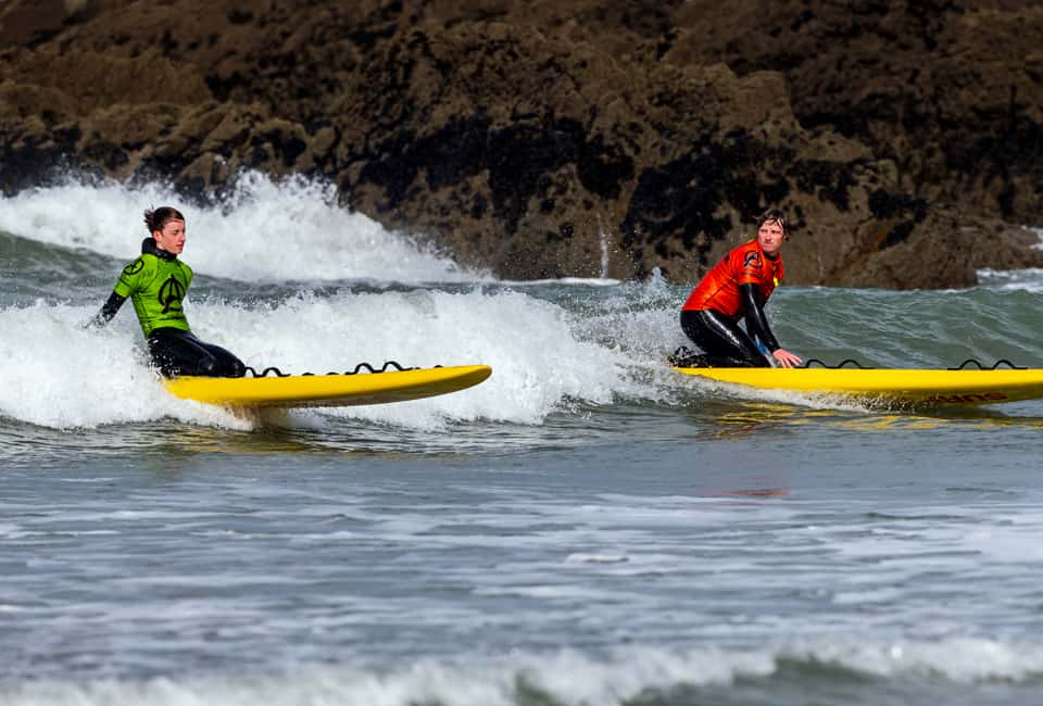 outdoor instructor training in surfing a rescue board back to shore