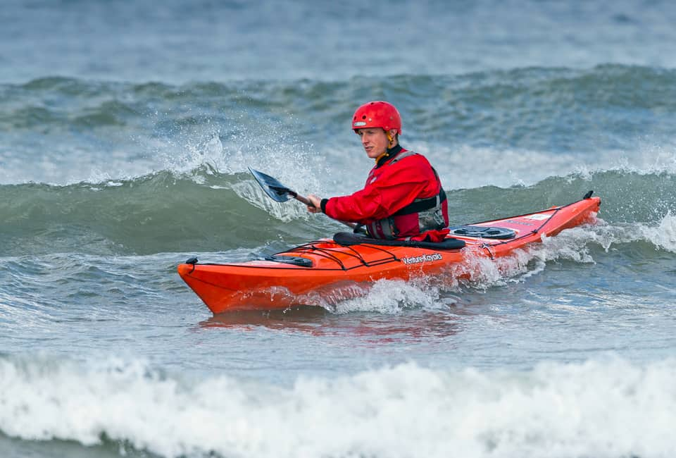outdoor instructor course group member surfing a sea kayak