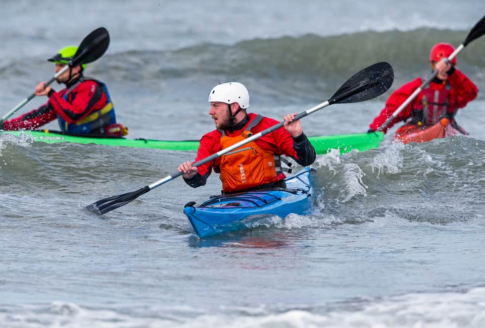 outdoor instructor training group learning to surf sea kayaks