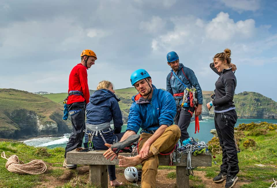 outdoor instructor training group relaxing on cliff top in Cornwall