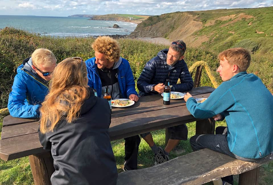 outdoor instructor course group enjoying their meal overlooking the ocean